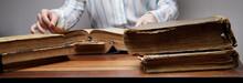 The Hands Of An Invisible Person Leaf Through The Pages Of An Old Book Lying On A Wooden Table In A University Or School Library.vintage Paper Texture. Selective Focus