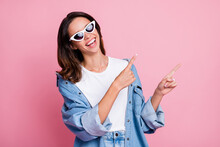Photo Of Charming Shiny Lady Dressed Jeans Clothes Dark Eyewear Pointing Two Fingers Empty Space Isolated Pink Color Background