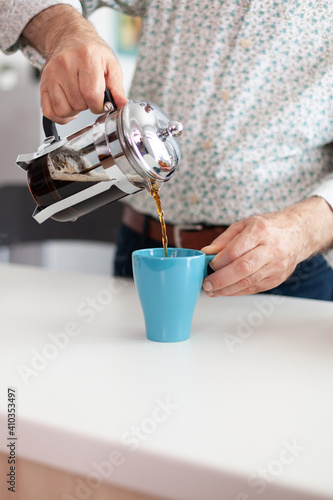 Obraz Elderly man making coffee using french press during breakfast in kitchen and pouring it in blue cup. Old person in the morning enjoying fresh brown cafe espresso cup caffeine, filter relax refreshment - fototapety do salonu