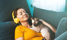 A Beautiful Girl Lies On A Sofa In Headphones In An Embrace With A Cat