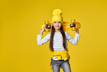 Little Child Girl In Hat Posing With Yellow Skateboard On Yellow Background.
