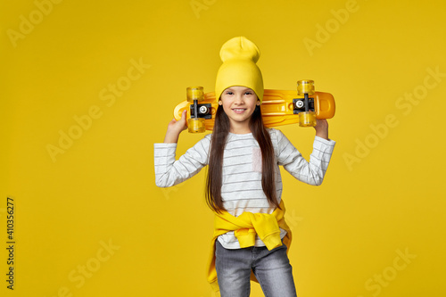 Photo little child girl in hat posing with yellow skateboard on yellow background