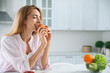 Concept of choice between healthy and junk food. Woman eating croissant at white table in kitchen