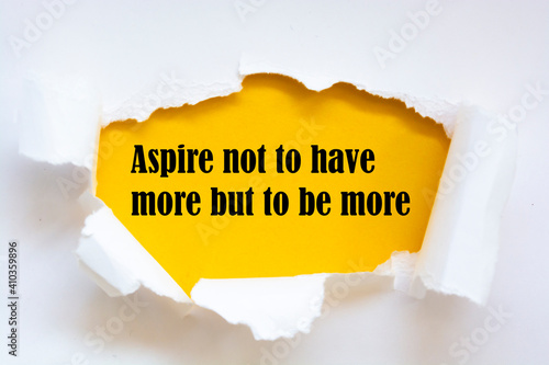 Aspire not to have more but to be more. Words written under torn paper. Motivation concept text.