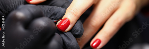 Fotografie, Obraz Close-up of manicure master painting clients nails in red colour