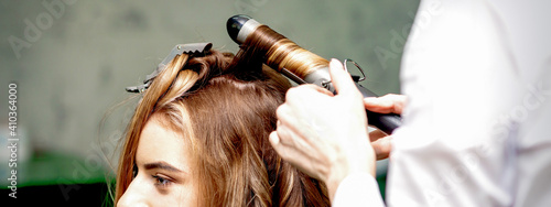 Cuadros en Lienzo Professional hairdresser makes curls with a curling iron for a young woman with