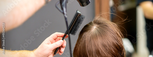 Fototapeta Hairdresser dries brown hair of the young woman in a beauty salon
