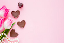 Tulips With Brown Black Chocolate Hearts And White Beads On Light Pink Table Background. Pastel Color. Closeup. Empty Place For Emotional, Sentimental Text, Lovely Quote Or Sayings. Top Down View.