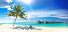 Beautiful Beach With White Sand, Turquoise Ocean, Palm And Blue Sky With Clouds On Sunny Day. Man Sits On Sand In Shade Of Palm Tree. Sun Is At Its Zenith. Summer Tropical Landscape, Panoramic View.