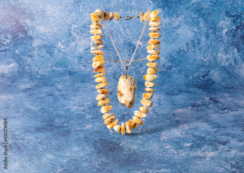 Luxurious necklace and pendant made of natural rare Baltic  white royal amber stone on a blue surface Fototapete