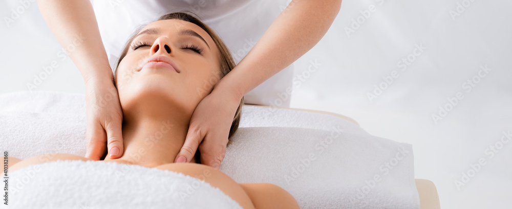 Fototapeta masseur doing neck massage to client with closed eyes in spa salon, banner
