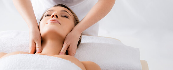 masseur doing neck massage to client with closed eyes in spa salon, banner
