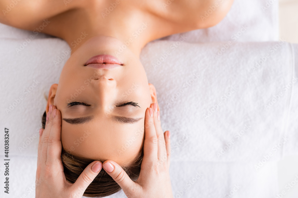 Fototapeta top view of masseur doing facial massage to woman in spa salon