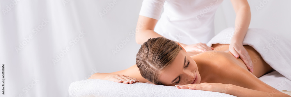 Fototapeta masseur massaging pleased young woman on massage table in spa salon, banner