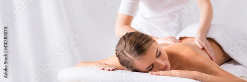 masseur massaging pleased young woman on massage table in spa salon, banner