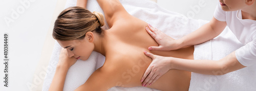 high angle view of happy masseur massaging back of young client on massage table, banner