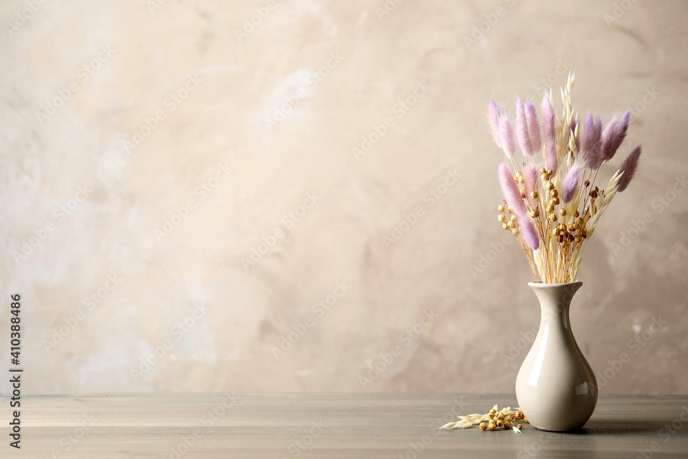 Fototapeta Dried flowers in vase on table against light grey background. Space for text