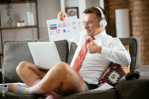 Businessman working online, wearing suit and no pants. Young man having video call. Businessman working at home.