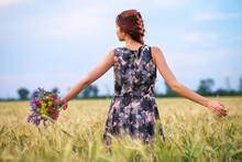 Beauty Girl Outdoors Enjoying Nature. Beautiful Teenage Model Girl In Dress On The Spring Field