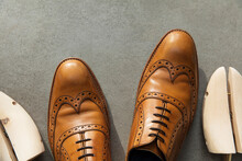 Overhead View Of A Pair Of Tan Brown Leather Mens Formal Shoes On Concrete