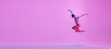 Young And Graceful Ballet Dancer Isolated On Pink Studio Background In Neon Light. Art, Motion, Action, Flexibility, Inspiration Concept. Flexible Caucasian Ballet Dancer, Moves In Glow. Flyer