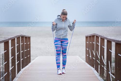 ragazza bionda con abbigliamento sportivo si allena con la corda vicino a una sp Wallpaper Mural