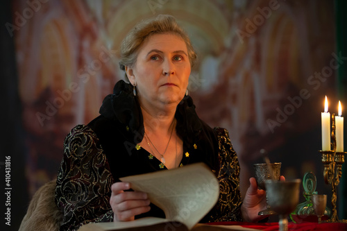 Fotografia Elderly beautiful woman with an old book and a silver goblet against the background of a blurred medieval castle