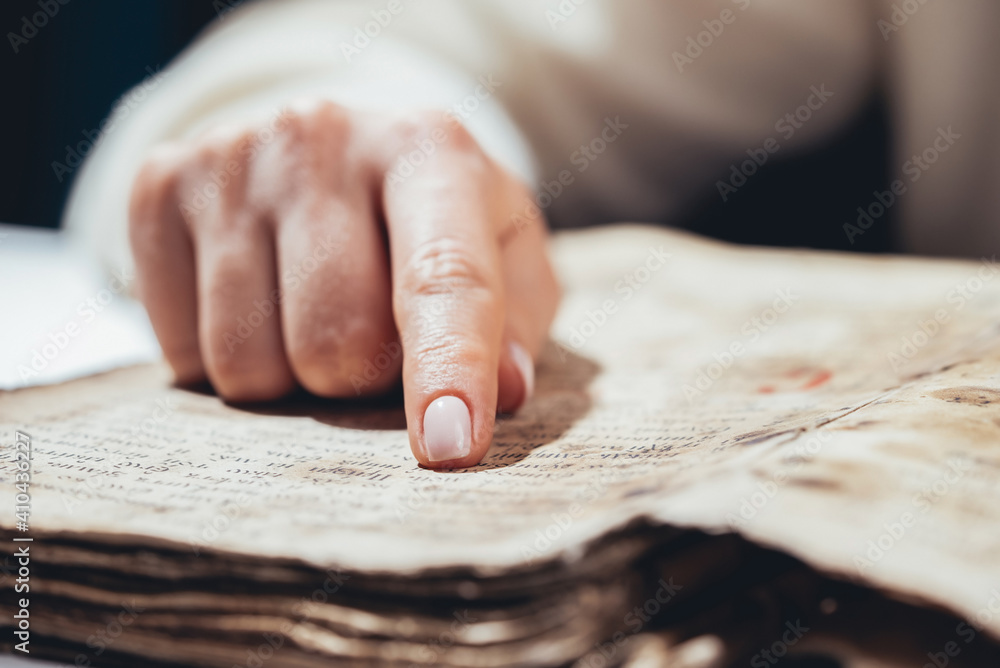 Fototapeta Woman reading ancient book - Bible. Concentrated attentively follows finger on paper page in library. Old archival manuscripts. History concept.
