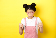 Sad Miserable Girl With Glamour Bright Makeup, Looking And Pointing Down Upset, Showing Bad Thing, Standing Against Yellow Background