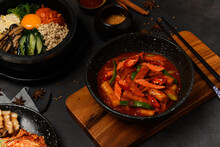 Korean Food Style : Top View Of Hot And Spicy Stir-fried Rice Cake ( Tteokbokki ) Put In The Black Bowl Or Dish And Placed On A Wooden Tray.