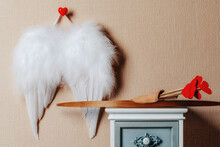 Angel Wings Hanging On The Wall . Cupid Weapons Set Bow And Arrows On The Nightstand. Valentines Day Concept.