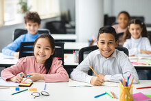 Portrait Of Small Girl And Boy Sitting At Desk In Classroom