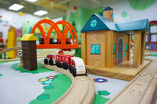 Wooden Train, House, And Railroad Toys In Indoor Playground