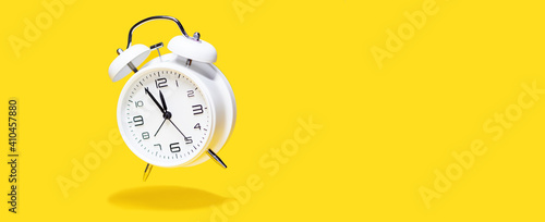 Photo White bell alarm clock hovering over yellow background