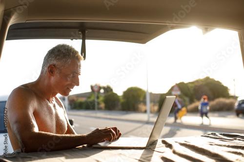 Fototapeta Uomo a torso nudo in contesto vacanziero lavora al computer nel cofano del suo furgone obraz