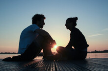 Couple Looking At Each Other During A Sunset In Front Of The Sea