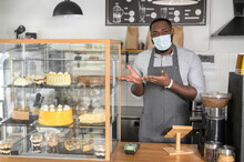 An African American Male Waiter At The Counter Wearing Medical Mask Points To Fresh Pastry And Cakes On The Showcase. A Protective Measures For Cafe Staff During Lockdown, Pandemic, Epidemic