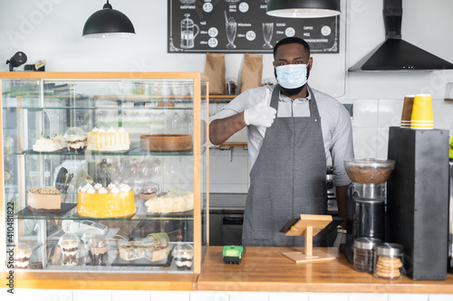 Fotomural An African-American male waiter, cafe owner wearing mask and gloves stands and shows thumb up behind the counter