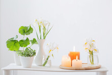 Burning Candles And Spring Flowers On Wooden Shelf In White Interior
