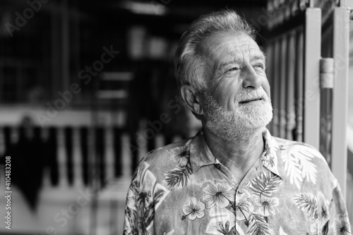 Obraz Close up of happy senior bearded tourist man smiling and thinking while looking up ready for vacation outdoors - fototapety do salonu