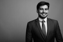 Young Handsome Bearded Persian Businessman Against Gray Background