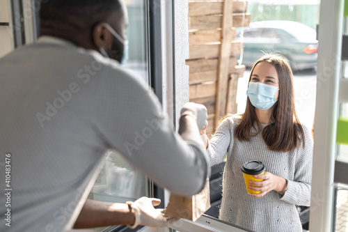 A male cafe worker gives a package with order and cup of takeaway coffee through a window to female customer wearing mask, small business works in conditions coronavirus pandemic © Вадим Пастух