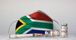 canvas print picture - A syringe, vials of COVID-19 vaccine and a medical face mask with the national flag of South Africa printed on the front side. 3D illustration