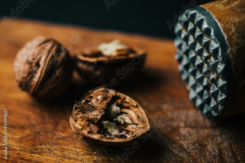 Canvas Print Closeup of cracked walnuts with a hammer on the table with a blurry background