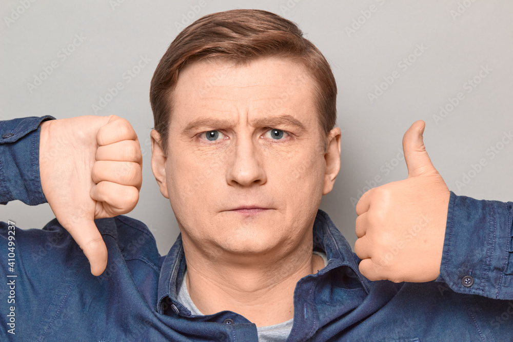 Fototapeta Portrait of serious man showing thumb up and thumb down gestures