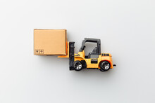 Mini Model Of Forklift With Carton Box Isolated On White Background. Logistics And Delivery Concept. Top View.