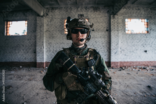 Fototapeta Military man with assault rifle standing inside building, he is ready for combat