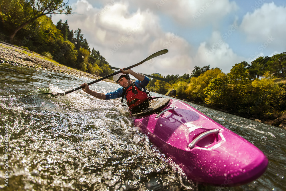 Fototapeta Whitewater kayaking, extreme sport rafting. Guy in kayak sails mountain river.