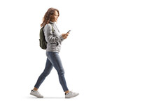 Teenage Girl With A Backpack Walking And Typing On A Mobile Phone