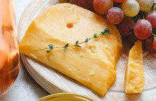 Cheddar Cheese With Grapes, Pink Wine, Honey. Wine Cheese Snacks For A Romantic Dinner. Aged Dutch Gouda Cheese On Cheeseboard With Cumin Herbs On Table.